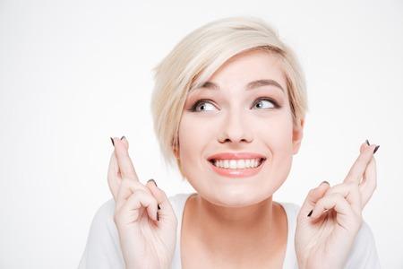 Close-up portret van een lachende vrouw met gekruiste vingers gebaar geïsoleerd op een witte achtergrond