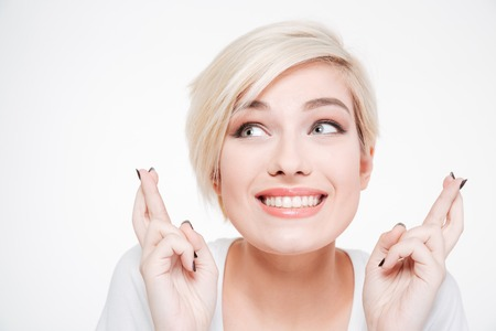 fingers: Closeup portrait of a smiling woman with fingers crossed gesture isolated on a white background