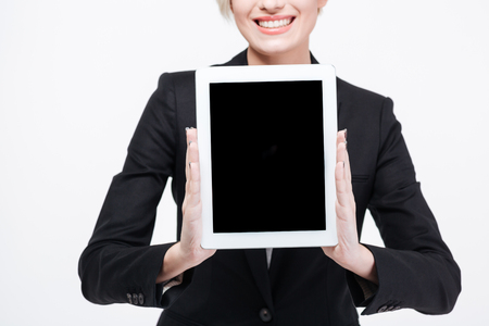computer isolated: Cropped image of a happy businesswoman showing blank tablet computer screen isolated on a white background Stock Photo