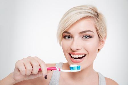 Happy schöne Frau Zähneputzen auf einem weißen Hintergrund