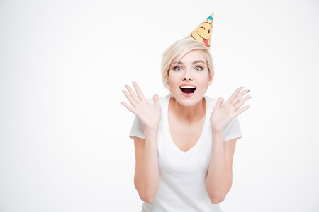Happy amazed woman in party hat looking at camera isolated on a white background