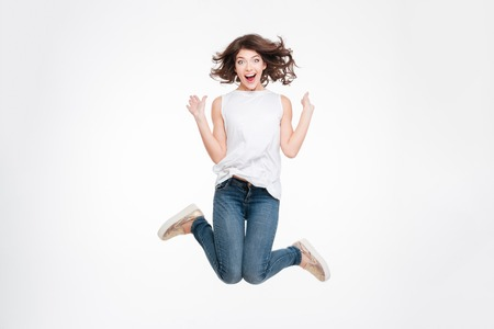 Full length portrait of a cheerful cute woman jumping isolated on a white background
