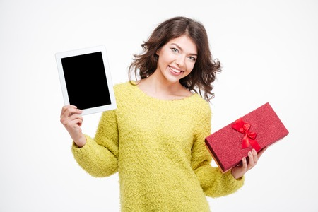 blank tablet: Happy woman showing blank tablet computer screen and holding gift box isolated on a white background