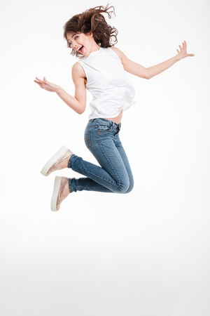 jumping: Retrato de cuerpo entero de una mujer alegre saltando aislado en un fondo blanco