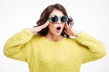 Amazed woman in sunglasses standing isolated on a white background
