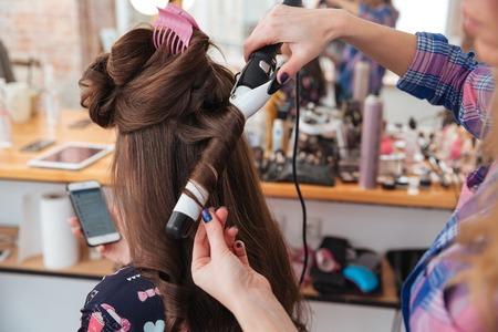 Mujer peluquería haciendo corte de pelo usando rizador de pelo largo de la mujer joven con el teléfono inteligente en salón de belleza