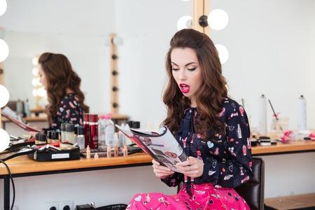 Verbaasde mooie jonge vrouwenzitting in schoonheidssalon en het lezen van maniertijdschrift