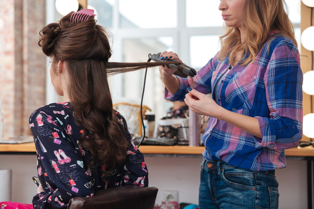 straightener: Woman hairdresser standing and using hair straightener for long hair of young female in beauty salon