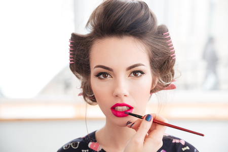 visagist: Portrait of young woman in curlers with makeup made by professional visagist Stock Photo