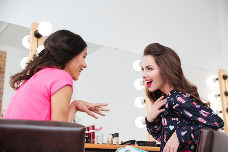 astonishment: Two excited wondered young women talking near the mirror in beauty salon Stock Photo