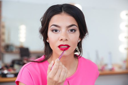 putting lipstick: Tender attractive young woman putting on red lipstick with brush