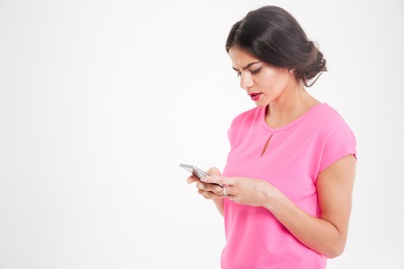 Unhappy frowning young woman using smartphone over white background
