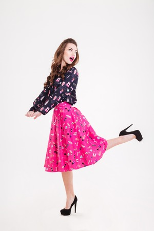 wondered: Amazed cute playful young woman in black high heels shoes  posing over white background