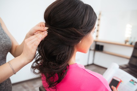 Back view of hairstyle of young woman with curly dark hair made by female hair stylist in beauty salon