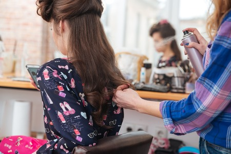 hairspray: Woman hair stylist applying hairspray to long hair of young female with cell phone in beauty salon