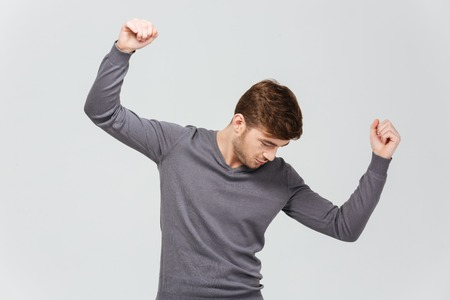pullover: Attractive young man in grey pullover dancing over white background