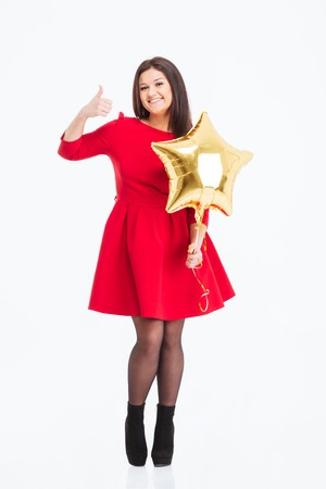 posing  agree: Full length portrait of a happy woman in red dress holding balloon and showing thumb up isolated on a white background