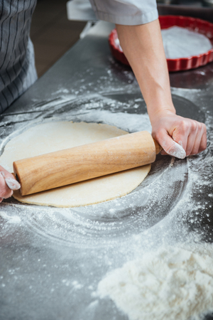 cook out: Hands of cook using wooden rolling pin for rolling out dough on the table Stock Photo