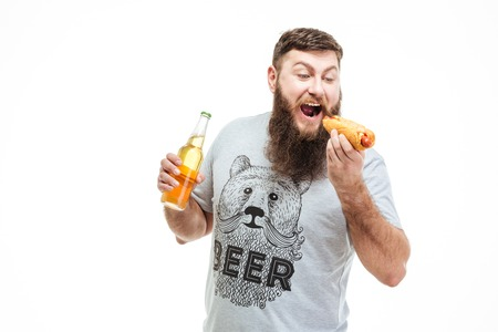 Handsome bearded man holding bottle of beer and eating hot dog over white background