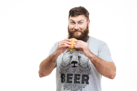 mouth smile: Smiling handsome man with beard standing and holding hamburger over white background Stock Photo