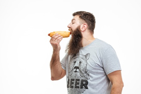 Profile of handsome man with beard standing and eating hot dog over white background
