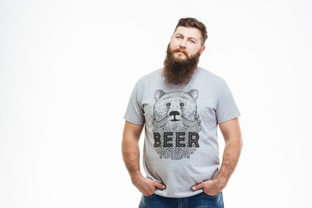 Serious attractive man with beard standing with hands in pockets over white background