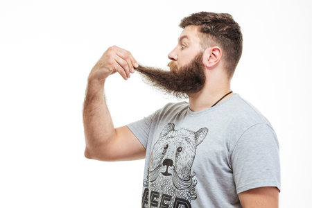 wondered: Profile of shocked wondered bearded man holding his beard over white background Stock Photo
