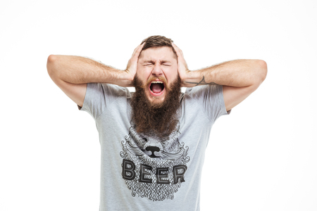 hands over ears: Depressed upset man with beard covered ears by hands and shouting over white background