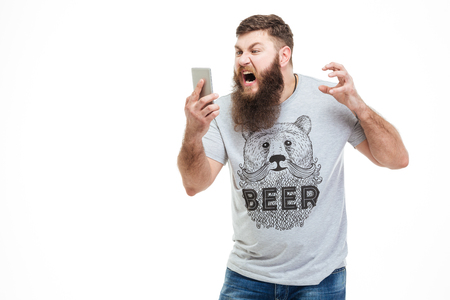 irritated: Irritated angry man with beard holding smartphone and shouting over white background