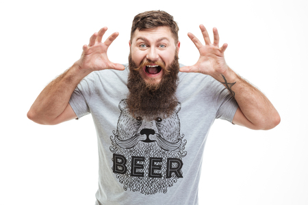 angriness: Mad brutal bearded man with raised hands growling and scaring over white background Stock Photo