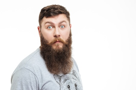 wondered: Portrait of amazed attractive man with beard over white background