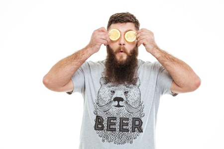funny bearded man: Funny bearded man covered eyes with two slices of lemon over white background