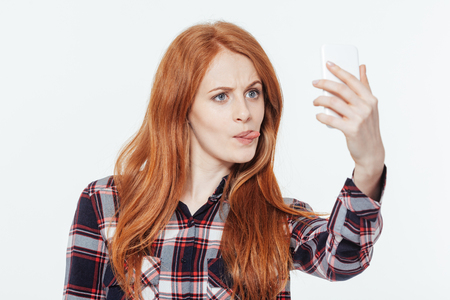 Funny redhead woman making selfie photo on smartphone isolated on a white background
