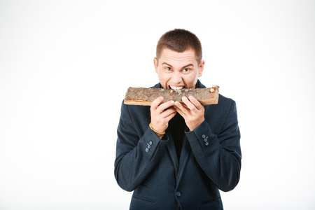 spite: Businessman biting wooden timber isolated on a white background