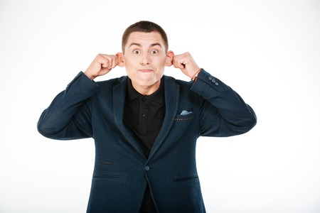 unsettled: Funny businessman holding his ears isolated on a white background Stock Photo