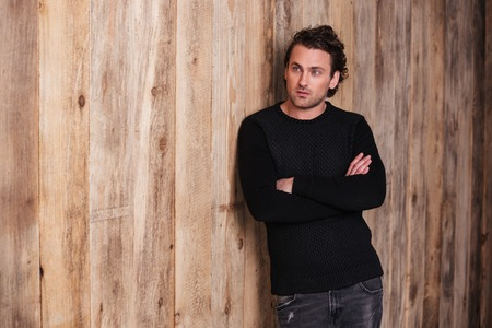 black sweater: Serious curly young man in black sweater standing with arms crossed over wooden background