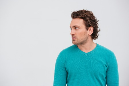 Profile of handsome curly young man standing and looking away over white background