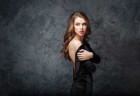 Beautiful tender young woman in black dress with open back over grey background