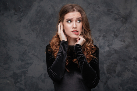 Portrait of scared confused young woman biting her lip over grey background Reklamní fotografie