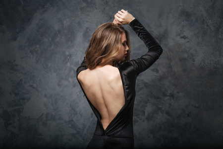 Back view of seductive young woman in evening dress with open back posing with raised hands over grey background Standard-Bild