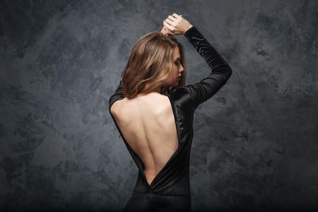 Vista trasera de la joven mujer seductora en vestido de noche con la espalda abierta posando con las manos levantadas sobre fondo gris Foto de archivo