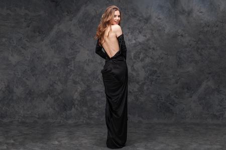 Hintere Ansicht der reizend verlockenden jungen Frau im langen Abendkleid mit dem offenen Rücken, der zurück über grauem Hintergrund schaut