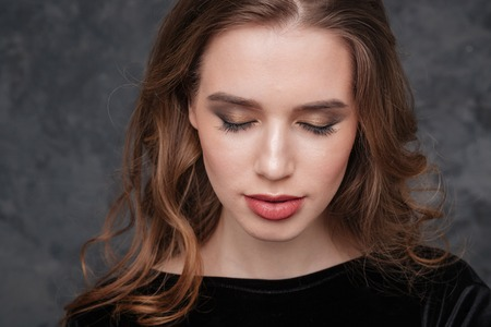 Closeup of beautiful young woman with closed eyes and modern makeup over grey background