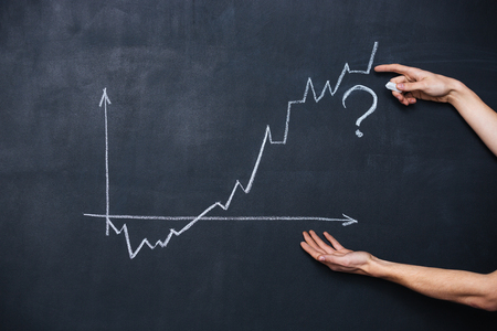 uncertainty: Decreasing and increasing graph showing uncertainty drawn on blackboard background Stock Photo