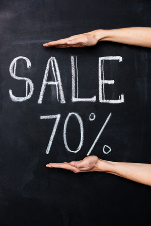 seventy two: Two hands showing seventy percent sale drawn on blackboard with chalk Stock Photo