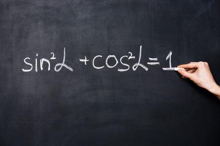 theorem: Hand writing trigonometry formula on blackboard with chalk