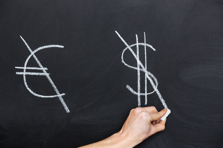 unbalanced: Signs of euro and dollar crossed on blackboard by hand with chalk