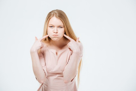 inflated: Woman with inflated cheeks posing isolated on a white background
