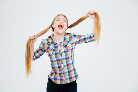 ponytails: Young woman holding her ponytails and screaming isolated on a white background Stock Photo