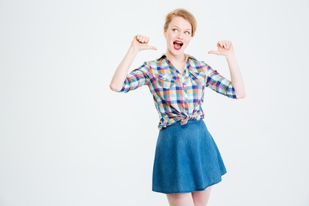 egocentric: Young woman pointing finger at herself isolated on a white background Stock Photo